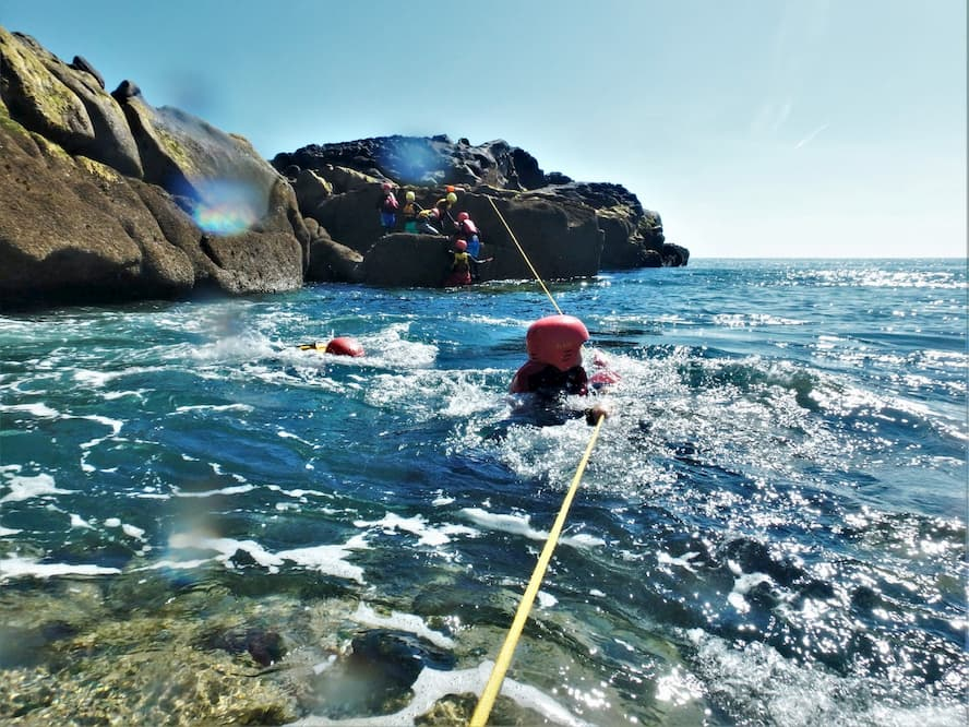 Crossing a gully using ropes coasteeringon the isles fo Scilly, Cornwall.jpg